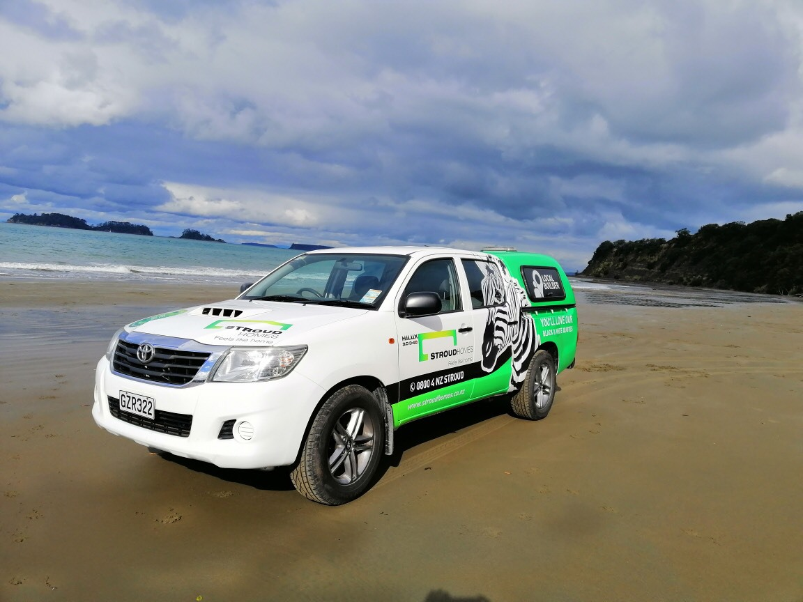 Stroud Homes branded ute on Auckland Beach
